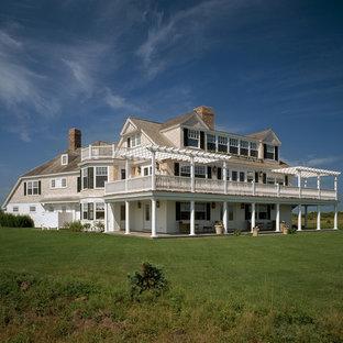 Imagen de fachada de casa beige, marinera, extra grande, de tres plantas, con revestimiento de madera y tejado de teja de madera