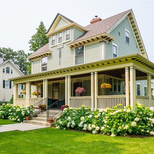 Example of a large transitional green two-story wood exterior home design in Minneapolis