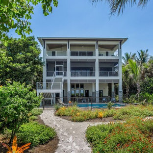 Inspiration for a tropical three-story exterior home remodel in Miami