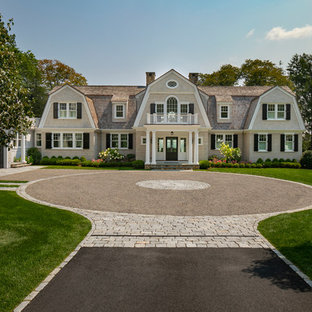 Example of a huge classic beige two-story stone house exterior design in Boston with a gambrel roof and a shingle roof