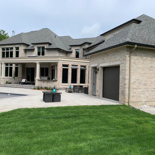 Example of a french country gray two-story stone house exterior design in Toronto with a hip roof and a shingle roof
