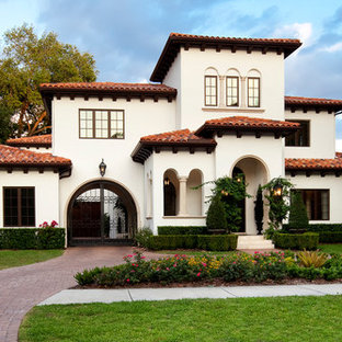 Tuscan white two-story exterior home photo in Tampa with a hip roof
