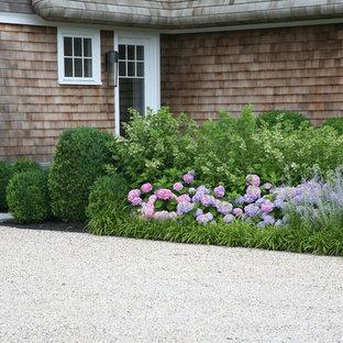 Imagen de fachada de casa beige, marinera, de dos plantas, con revestimiento de madera