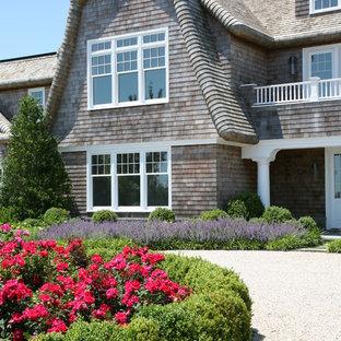 Ejemplo de fachada de casa marrón, costera, grande, de dos plantas, con revestimiento de madera, tejado a doble faldón y tejado de teja de madera