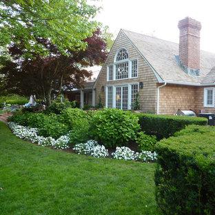 Imagen de fachada de casa beige, bohemia, extra grande, de una planta, con revestimiento de madera, tejado a dos aguas y tejado de teja de madera