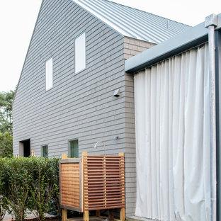 ニューヨークのコンテンポラリースタイルのおしゃれな家の外観 (木材サイディング、グレーの外壁、半切妻屋根、戸建、金属屋根) の写真