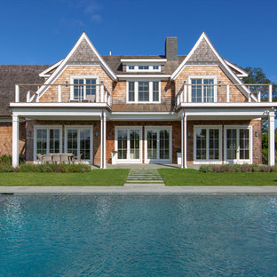 Inspiration for a beach style beige two-story wood exterior home remodel in New York with a shingle roof