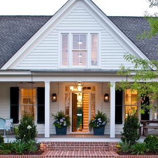 Стильный дизайн: двухэтажный, белый дом среднего размера в стиле кантри с облицовкой из винила и двускатной крышей - последний тренд