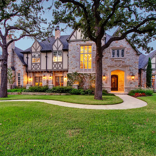 Example of a large classic two-story stone gable roof design in Dallas with a shingle roof