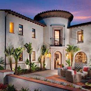 Modelo de fachada beige, de estilo americano, grande, de dos plantas, con revestimiento de estuco