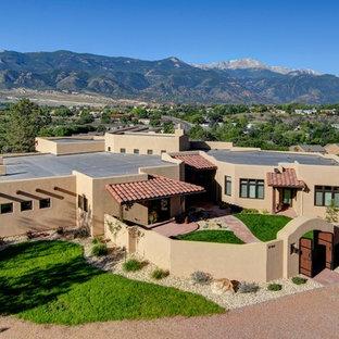 Diseño de fachada beige, de estilo americano, grande, de una planta, con revestimiento de estuco y tejado plano
