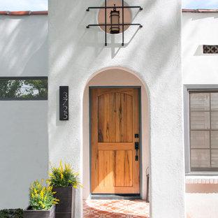 Imagen de fachada de casa blanca, mediterránea, grande, de una planta, con revestimiento de estuco, tejado plano y tejado de teja de barro