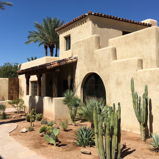 Expansive two-storey adobe beige house exterior in Phoenix with a hip roof and a tile roof.