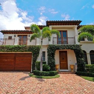 Inspiration for a large mediterranean white two-story stucco exterior home remodel in Miami with a tile roof