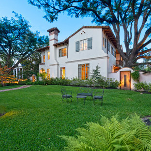 Large mediterranean white two-story stucco exterior home idea in Houston with a hip roof