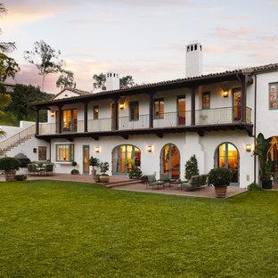 Exemple d'une grande façade de maison blanche méditerranéenne à un étage avec un revêtement en stuc et un toit à deux pans.