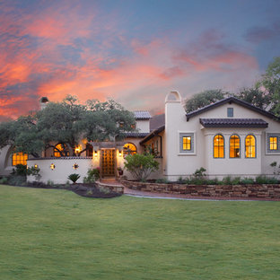 Large mediterranean white two-story stucco gable roof idea in Austin with a tile roof