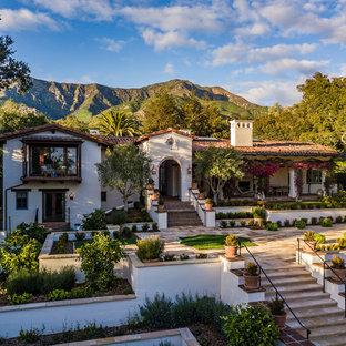 Modelo de fachada de casa blanca, mediterránea, grande, de dos plantas, con revestimiento de estuco, tejado a dos aguas y tejado de teja de barro