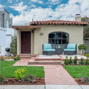 Ispirazione per la facciata di una casa piccola beige american style a un piano con rivestimento in stucco e tetto a mansarda