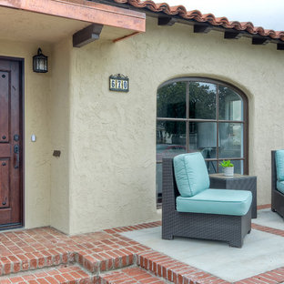 Small southwest beige one-story stucco exterior home photo in San Diego with a gambrel roof