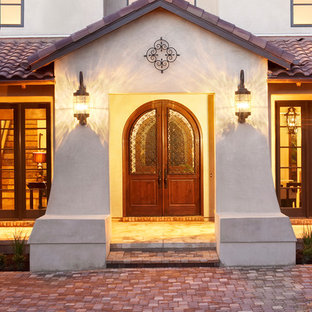 Imagen de fachada de casa blanca, mediterránea, extra grande, de dos plantas, con revestimiento de estuco, tejado a dos aguas y tejado de teja de barro