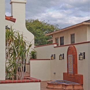 Diseño de fachada de casa blanca, mediterránea, grande, de tres plantas, con revestimiento de estuco y tejado a cuatro aguas