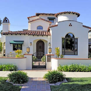 Large tuscan white three-story stucco house exterior photo in San Diego with a hip roof