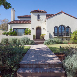 Example of a large tuscan beige two-story stucco exterior home design in Los Angeles with a tile roof