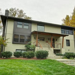 Modelo de fachada verde, bohemia, de tamaño medio, a niveles, con revestimiento de ladrillo y tejado a dos aguas