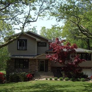 Modelo de fachada beige, de estilo americano, de tamaño medio, a niveles, con revestimientos combinados y tejado a dos aguas