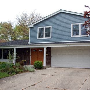 Foto de fachada de casa azul, clásica, de tamaño medio, a niveles, con revestimiento de aglomerado de cemento, tejado a dos aguas y tejado de teja de madera