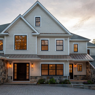 Example of a large transitional beige three-story exterior home design in New York with a shingle roof