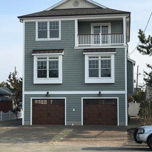 Immagine della facciata di una casa unifamiliare grigia american style a tre o più piani di medie dimensioni con rivestimento in vinile, tetto a capanna e copertura mista