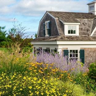 Réalisation d'une très grand façade de maison beige champêtre à un étage avec un revêtement en vinyle et un toit de Gambrel.