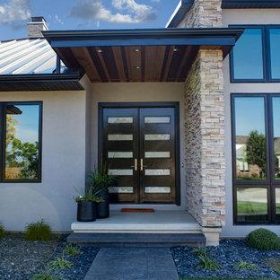 На фото: с высоким бюджетом двухэтажные фасады частных домов среднего размера бежевого цвета в стиле модернизм с облицовкой из цементной штукатурки, вальмовой крышей и металлической крышей