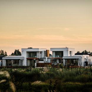 На фото: большой, двухэтажный, деревянный, серый дом в современном стиле с плоской крышей