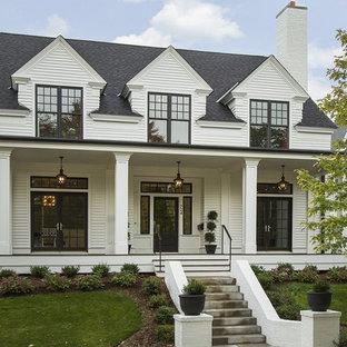 Foto de fachada blanca, clásica renovada, de tamaño medio, de dos plantas, con tejado a dos aguas y revestimiento de madera