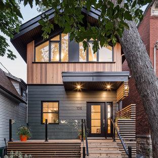 Modelo de fachada negra, minimalista, de tamaño medio, de dos plantas, con revestimiento de madera