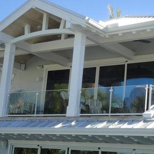 Imagen de fachada de casa gris, marinera, grande, de dos plantas, con revestimiento de estuco, tejado a cuatro aguas y tejado de metal
