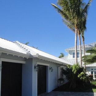 Diseño de fachada de casa gris, costera, grande, de dos plantas, con revestimiento de estuco, tejado a cuatro aguas y tejado de metal