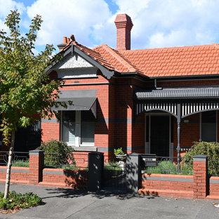 Exempel på ett mellanstort klassiskt rött hus, med allt i ett plan, tegel, valmat tak och tak med takplattor