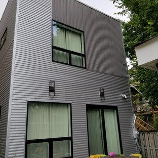 Ejemplo de fachada de casa gris, bohemia, de tamaño medio, con revestimiento de metal, tejado plano y tejado de varios materiales