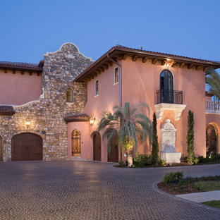 Large mediterranean pink two-story stucco exterior home idea in Orlando with a hip roof