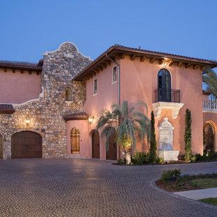 Idées déco pour une grand façade de maison rose méditerranéenne à un étage avec un revêtement en stuc et un toit à quatre pans.