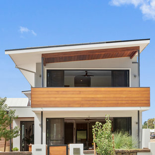 Photo of a contemporary two-storey stucco white house exterior in Perth with a shed roof.
