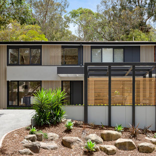 Photo of a large contemporary two-storey grey house exterior in Melbourne with a flat roof.