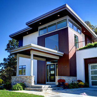 Large trendy white two-story mixed siding flat roof photo in Grand Rapids