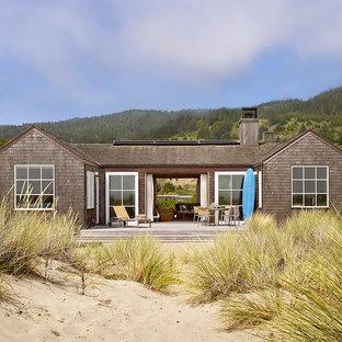 Diseño de fachada costera, pequeña, de una planta, con revestimiento de madera y tejado a dos aguas