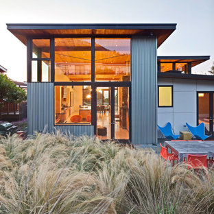 На фото: большой, двухэтажный, серый дом в морском стиле с облицовкой из металла и плоской крышей с
