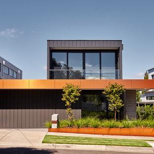 На фото: двухэтажный, серый частный загородный дом в современном стиле с облицовкой из металла и плоской крышей